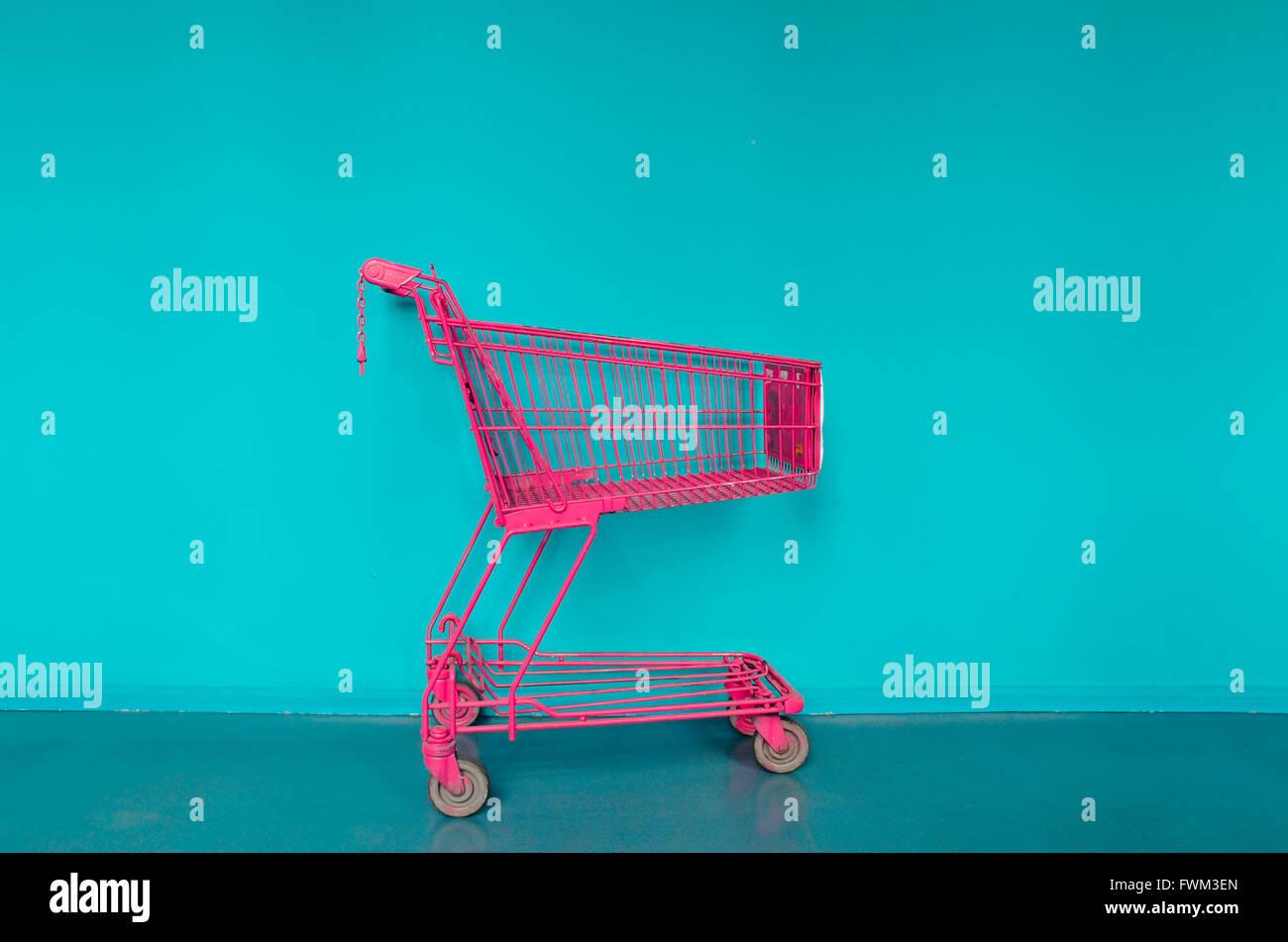 Einkaufswagen gegen blaue Wand Stockbild