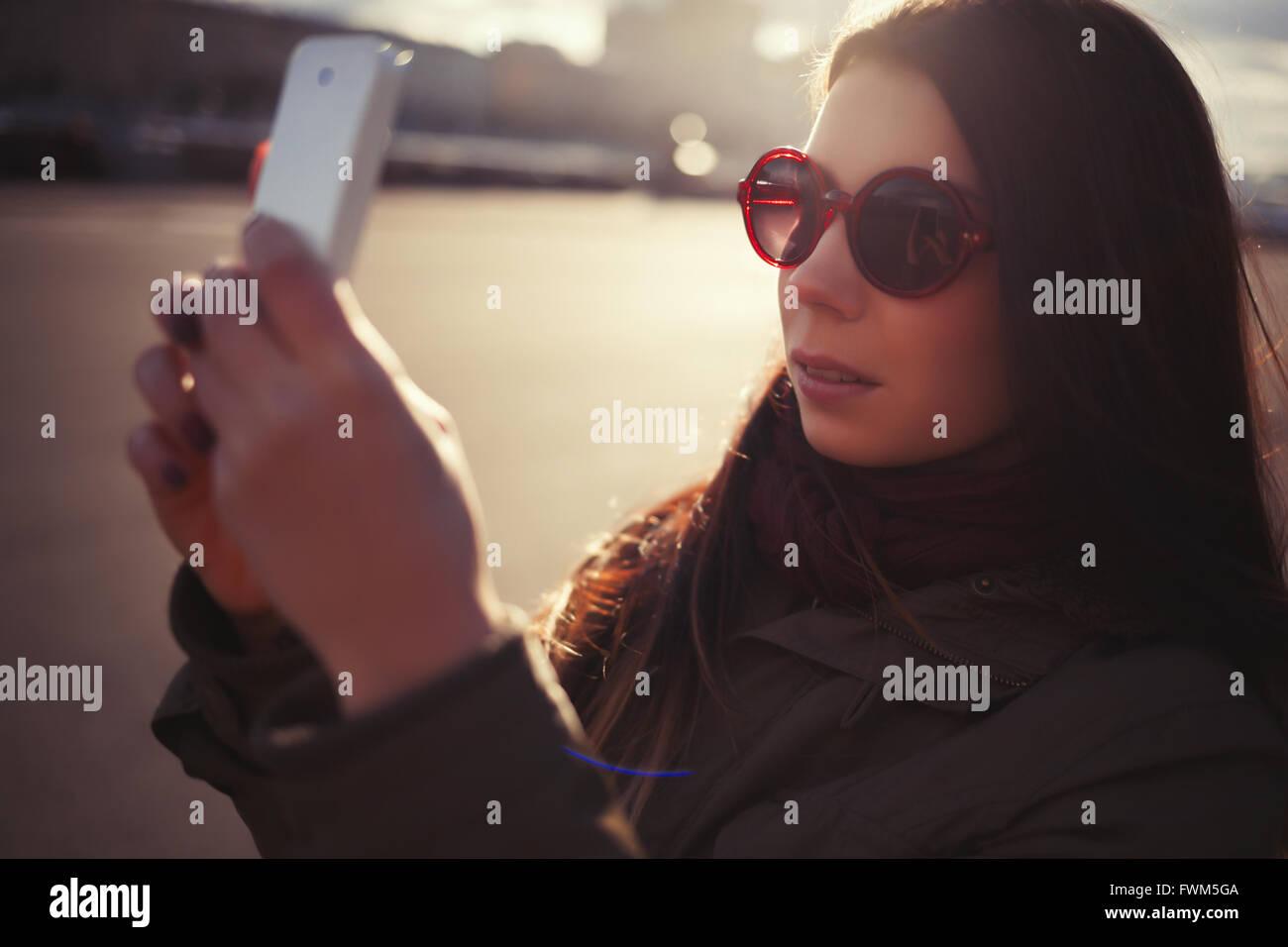 f721ad36b3ad Junge Hipster Mädchen in grauen Parka Mantel und Sonnenbrille Aufnahme mit  ihrem trendigen Smartphone im Freien
