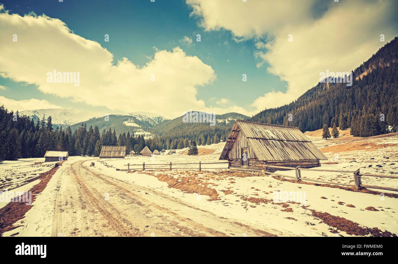Vintage getönten Holzhütten durch eine Straße im Tatra-Gebirge, Ende des Winters und Frühlingsbeginn, Stockbild