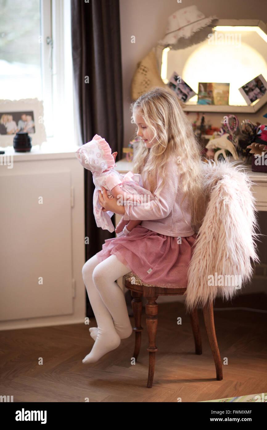 Mädchen spielen mit seiner Babypuppe. Tagespflege, Kind, Spielzimmer, behaupten Spiel. Stockfoto