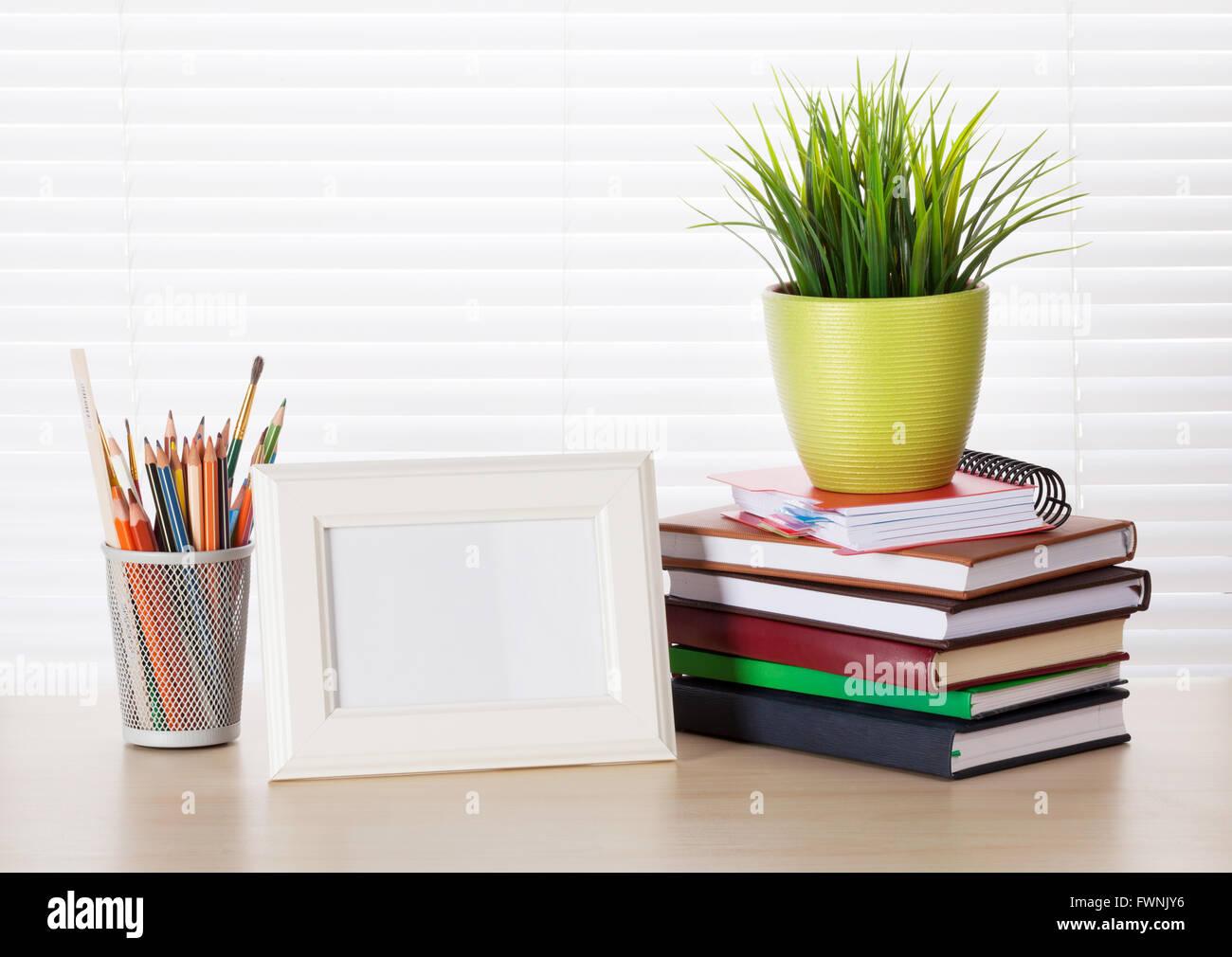 Büroarbeitsplatz mit Bilderrahmen, Bücher und Stifte auf Holz ...