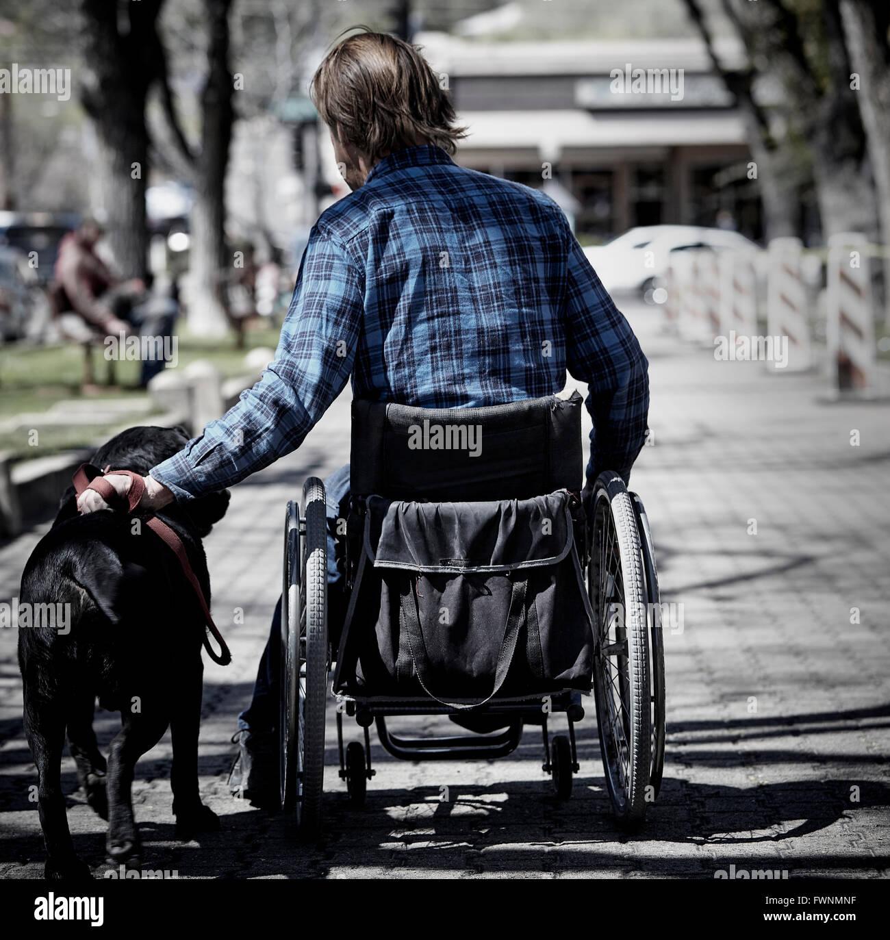 Prescott, Arizona, USA - 26. März 2016: Ein unbekannter Mann mit Rollstuhl und Blindenhund auf Bürgersteig Stockbild
