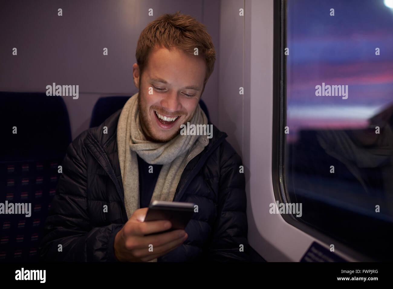 Mann sitzt im Zug Wagen senden SMS Stockbild