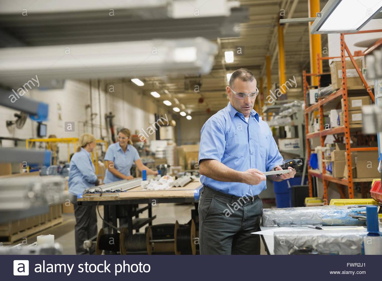 Arbeiter, die Metallteile im Werk zu prüfen Stockbild