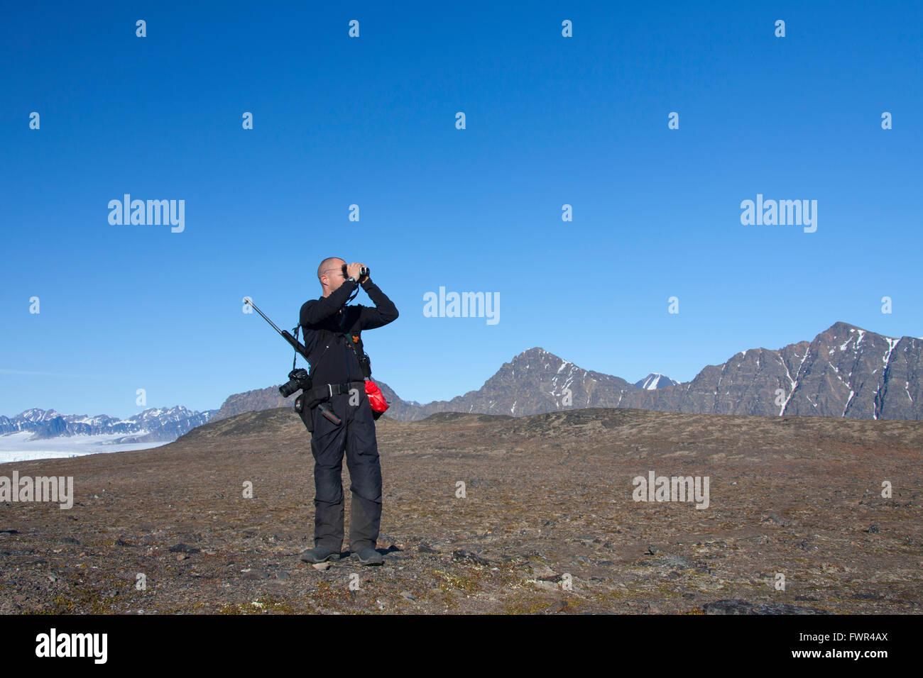 Eisbär-Wache, bewaffnet mit Gewehr auf der Suche nach Eisbären durch ein Fernglas, Spitzbergen, Norwegen Stockbild