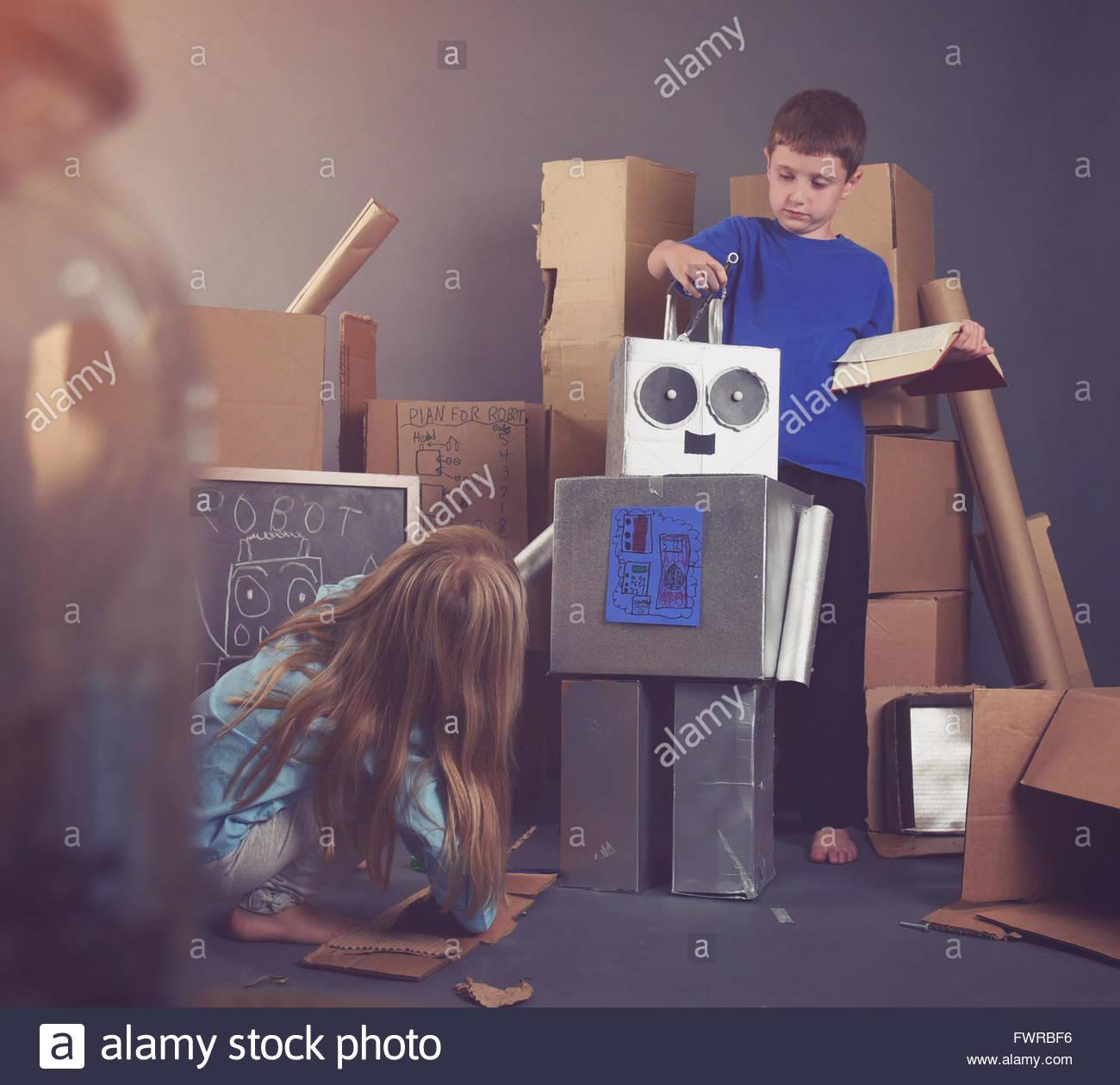 Zwei Kinder bauen einen Metall Roboter mit Werkzeugen und Bücher für eine Fantasie, Wissenschaft und Bildung Stockbild