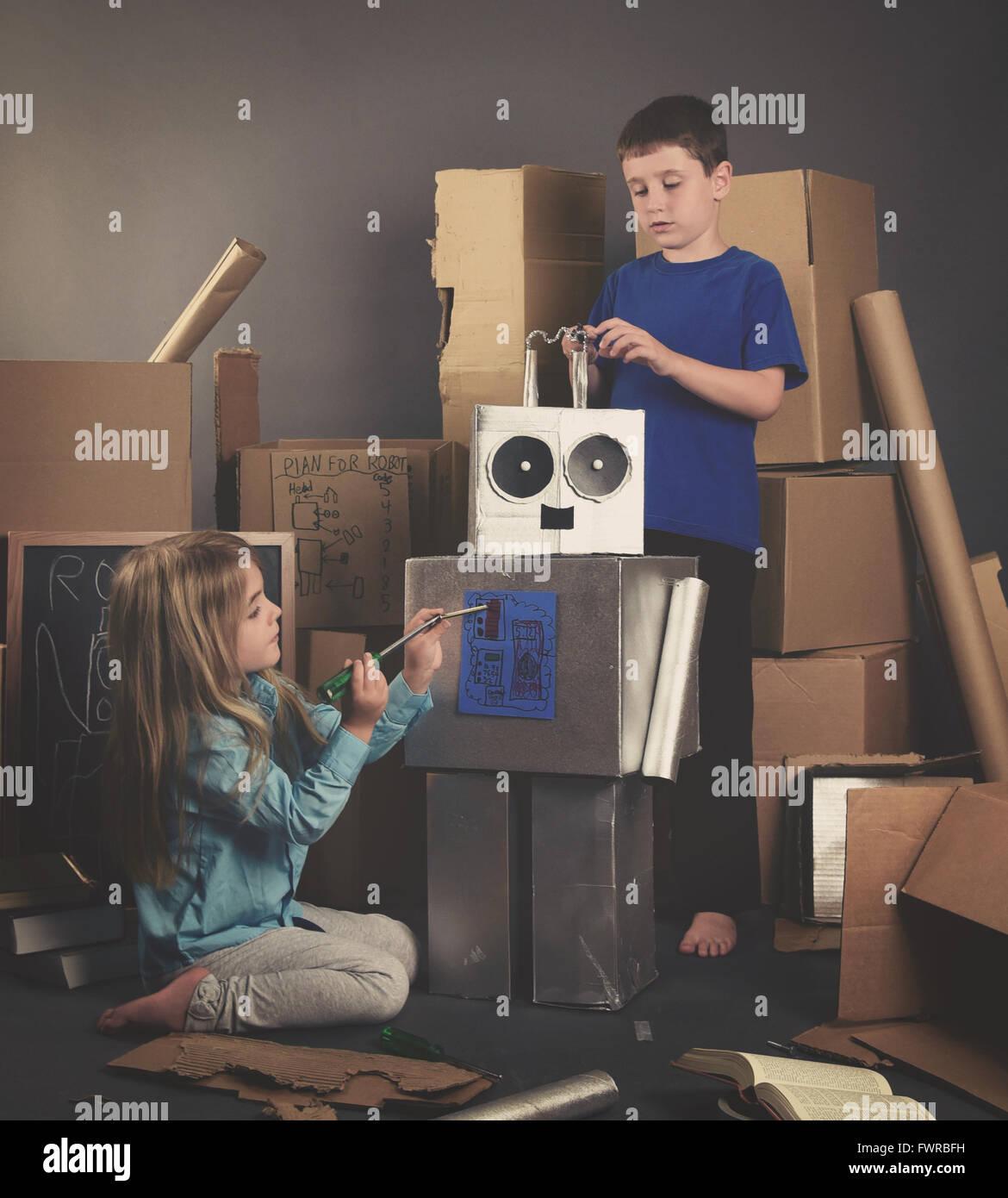 Kinder bauen einen Metall Roboter aus Pappkartons mit Werkzeugen und Bücher für eine Fantasie, Wissenschaft Stockbild