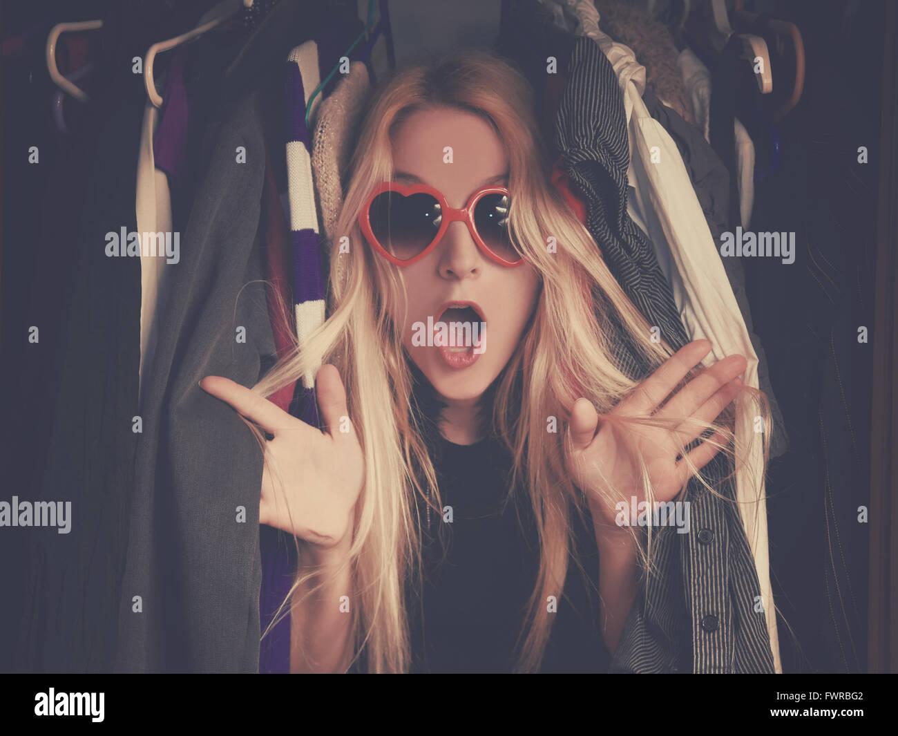 Eine Frau ist in einem Schrank unordentlich Kleidung mit roter Brille für einen Stil oder Mode Konzept überwältigt. Stockbild