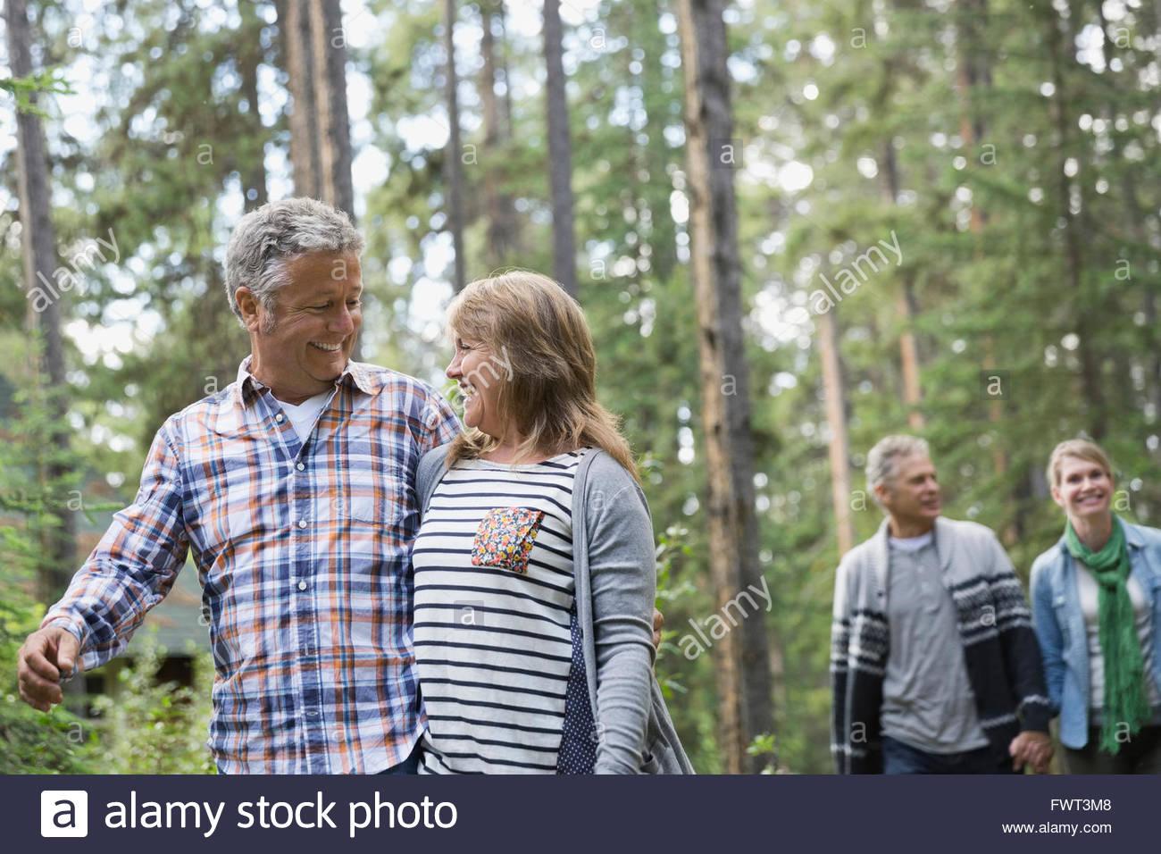 Lächelnde Paar mittleren Alters im Wald spazieren Stockbild
