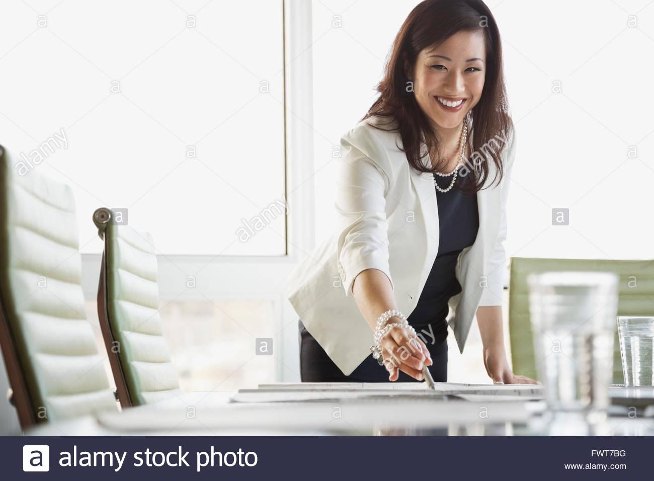 Porträt der Geschäftsfrau, die Überprüfung von Blaupause am Konferenztisch Stockbild