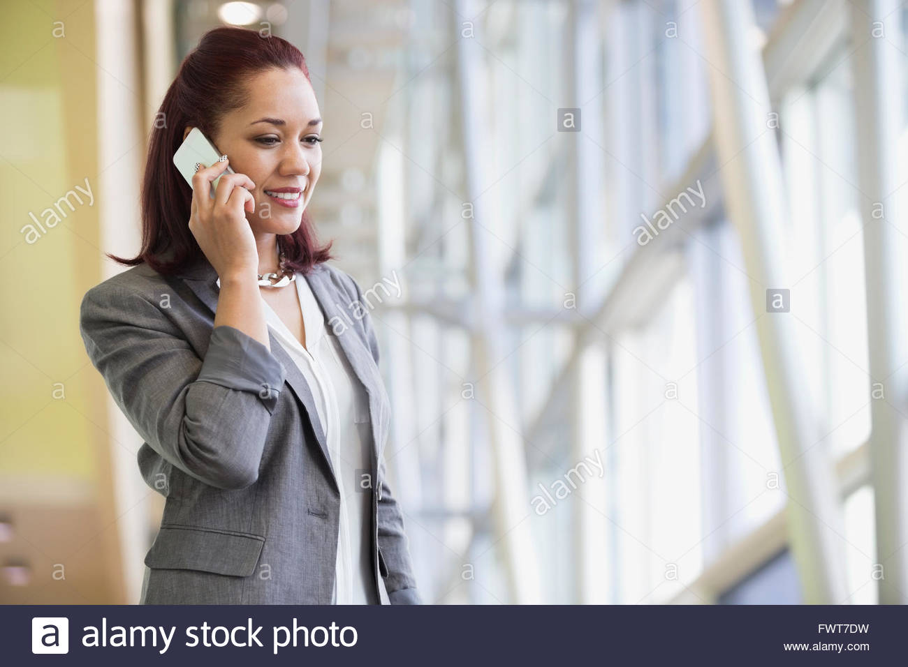 Junge Geschäftsfrau Beantwortung Handy im Büro Stockbild