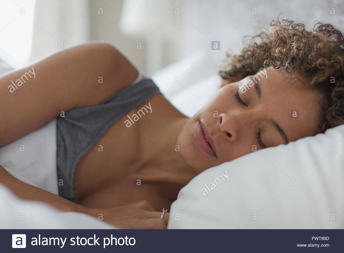Hübsche Frau im Bett ruhen. Stockbild