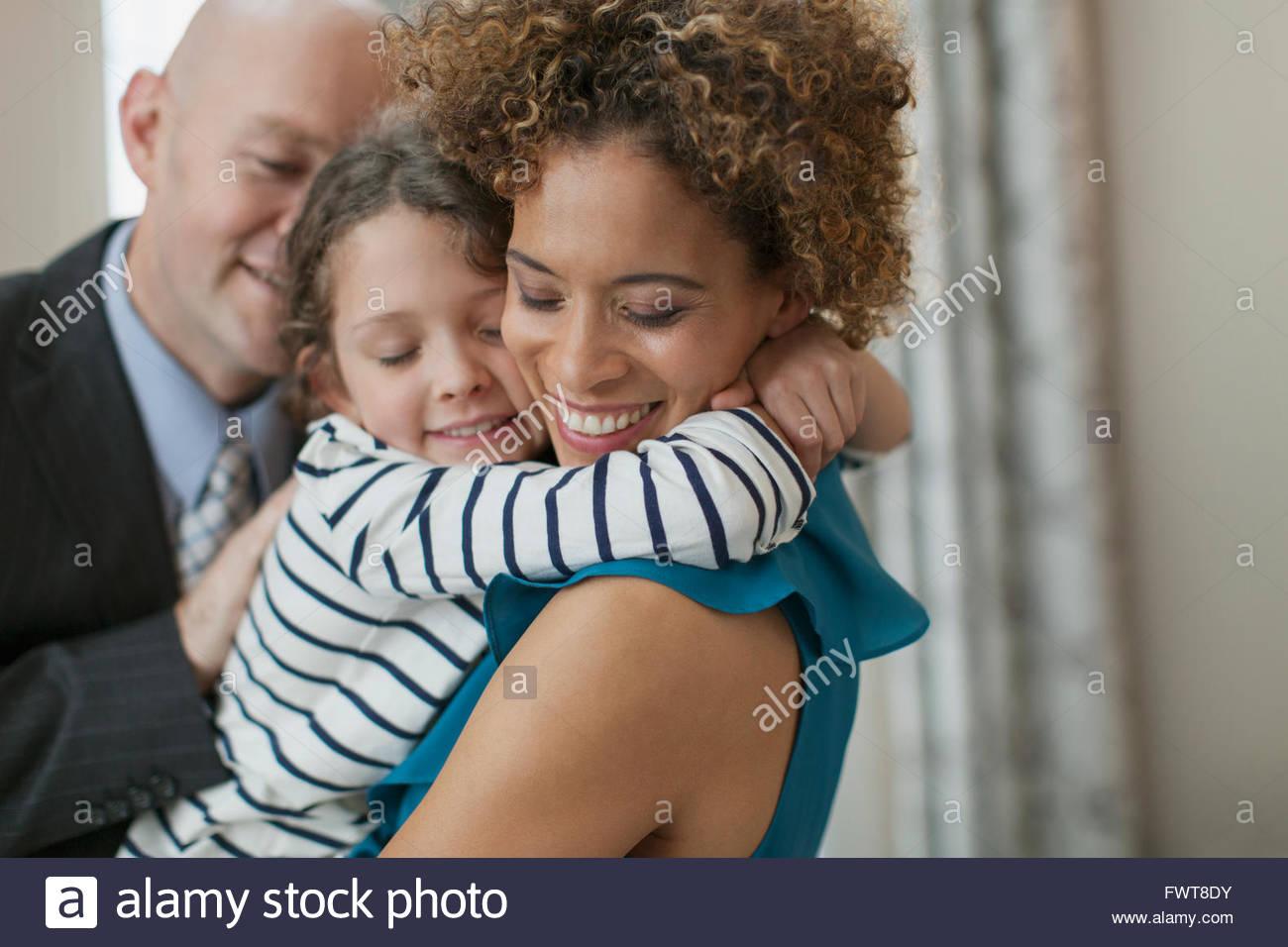 Junge Tochter Mutter liebevoll umarmt. Stockbild