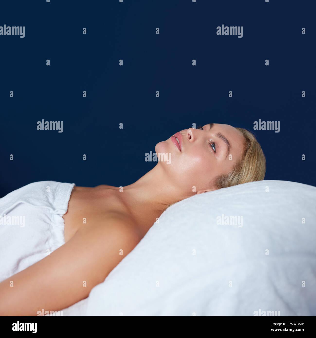 Innenaufnahme der attraktiven jungen Frau, die auf Massagetisch liegen. Kaukasische Frau eingehüllt in weißen Stockbild