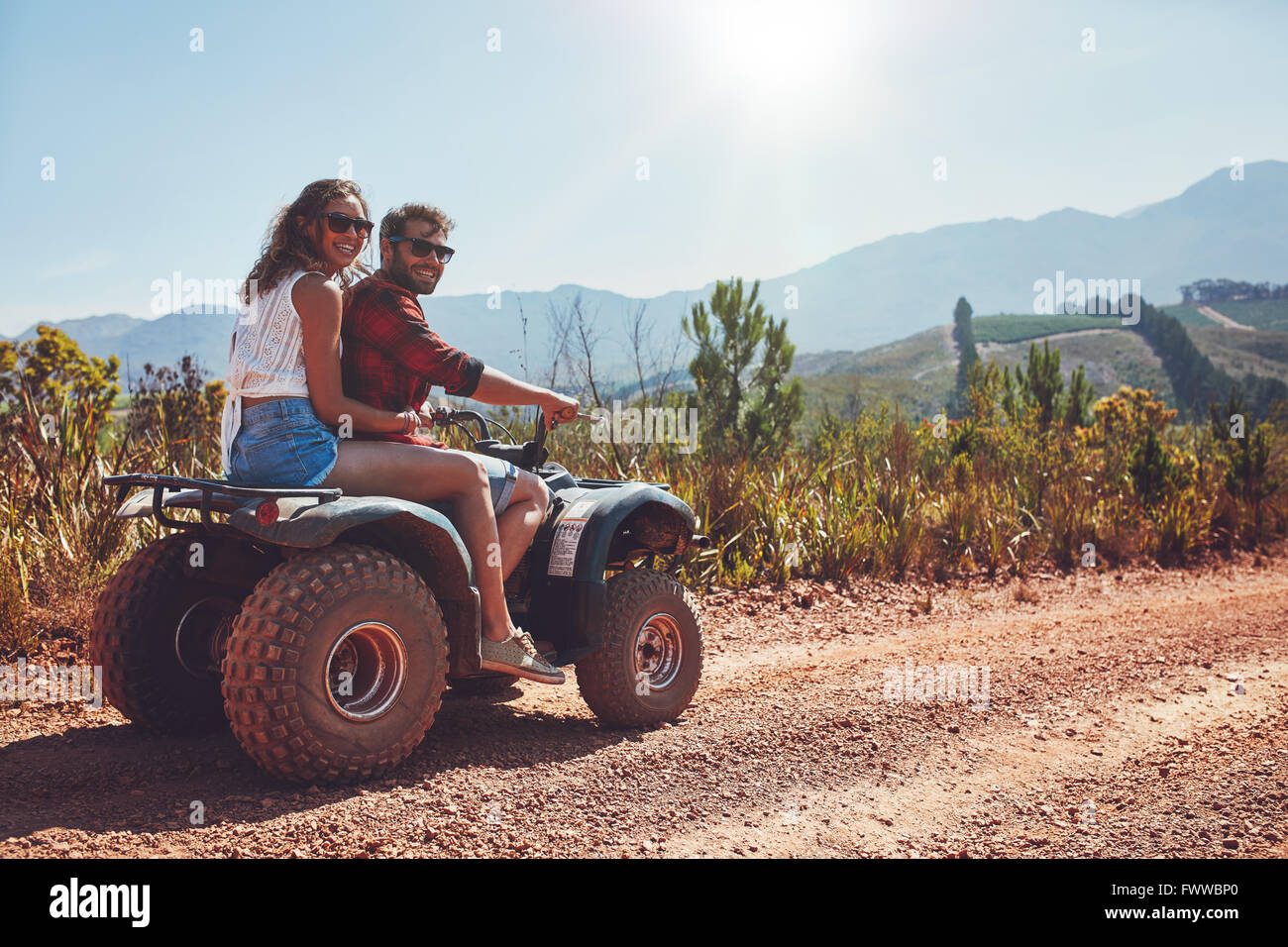 Porträt von Liebespaar in der Natur auf einer off-Road Fahrzeug. Junger Mann und Frau genießen ein Quad Stockbild