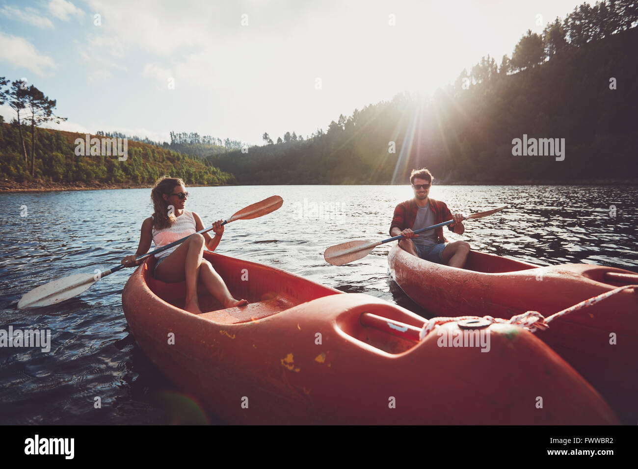 Junges Paar Kajakfahren auf dem See zusammen an einem Sommertag. Mann und Frau Kanu an einem sonnigen Tag. Genießen Stockbild