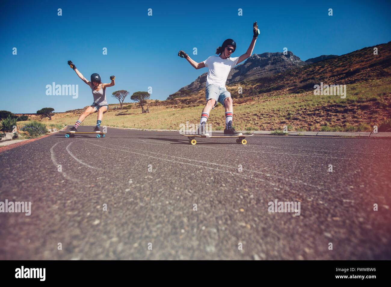 Junger Mann und Frau Skateboard auf der Straße. Junges Paar üben, Schlittschuhlaufen auf offener Straße. Stockbild