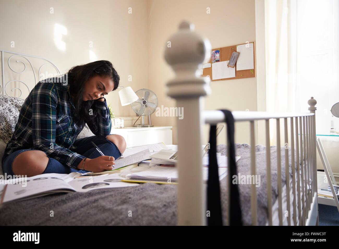Studentin, die an Studien im Schlafzimmer Stockbild