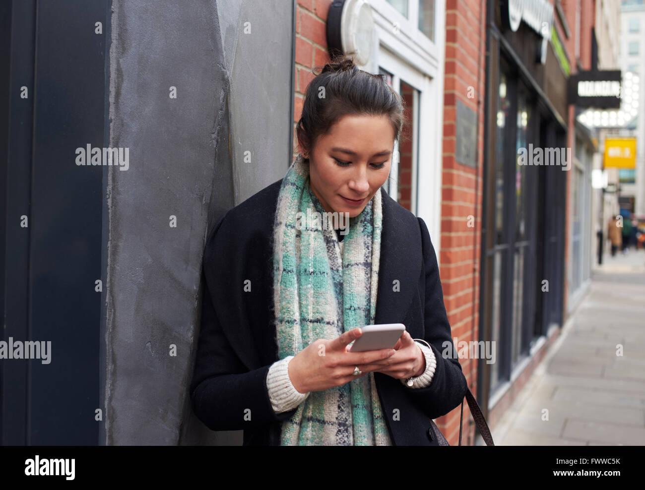Junge Frau liest Text-Messaging auf Stadtstraße Stockbild