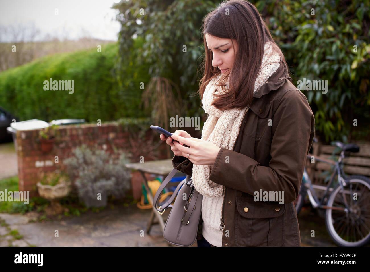 Junge Frau lesen SMS im freien Stockbild