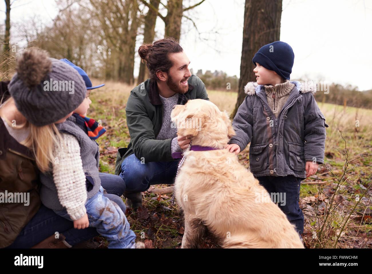 Familie mit Hund auf Winterspaziergang im Land spielen Stockbild