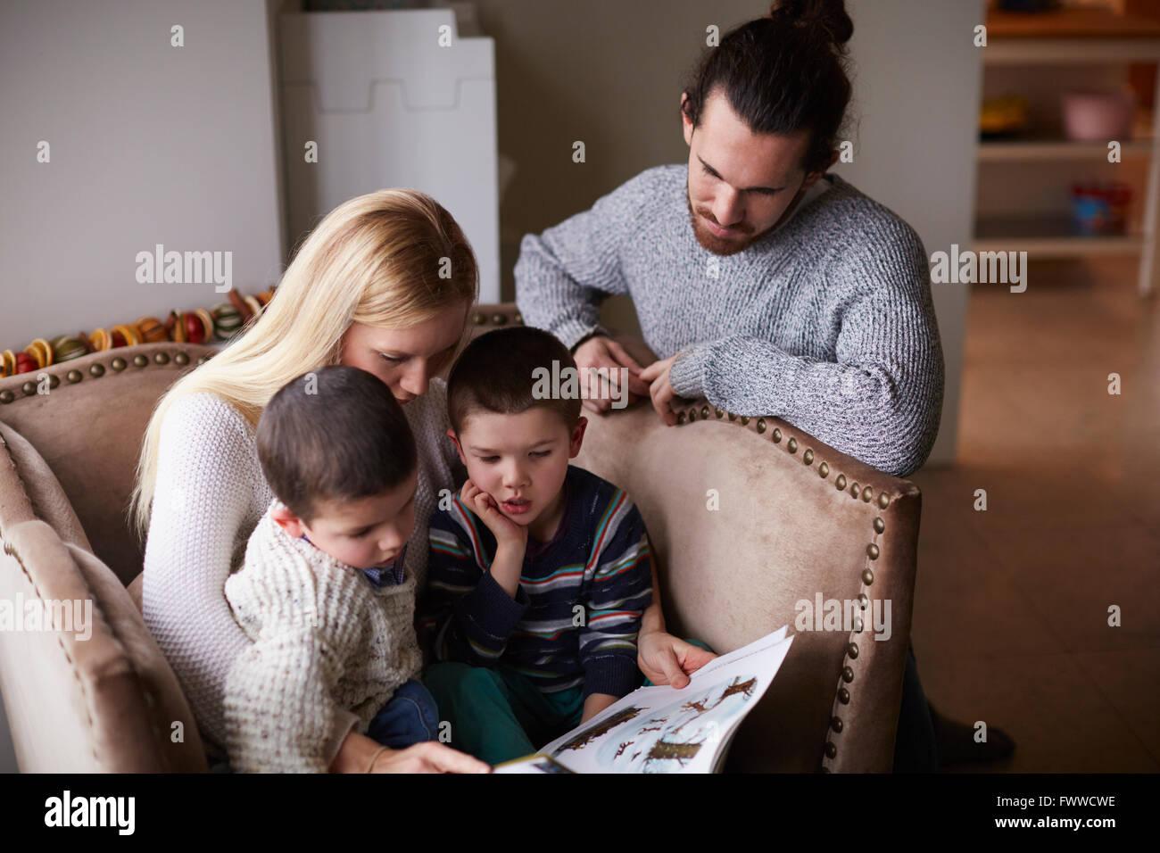Eltern sitzen im Stuhl zu Hause lesen Geschichte Söhnen Stockbild