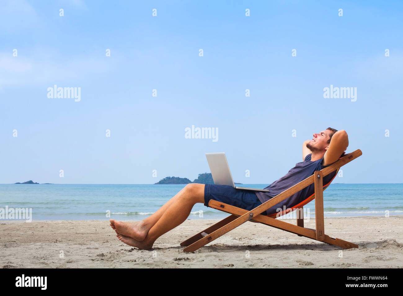 Freiberufler, glücklich erfolgreicher Geschäftsmann mit Laptop am Strand, blauer Himmel Stockbild