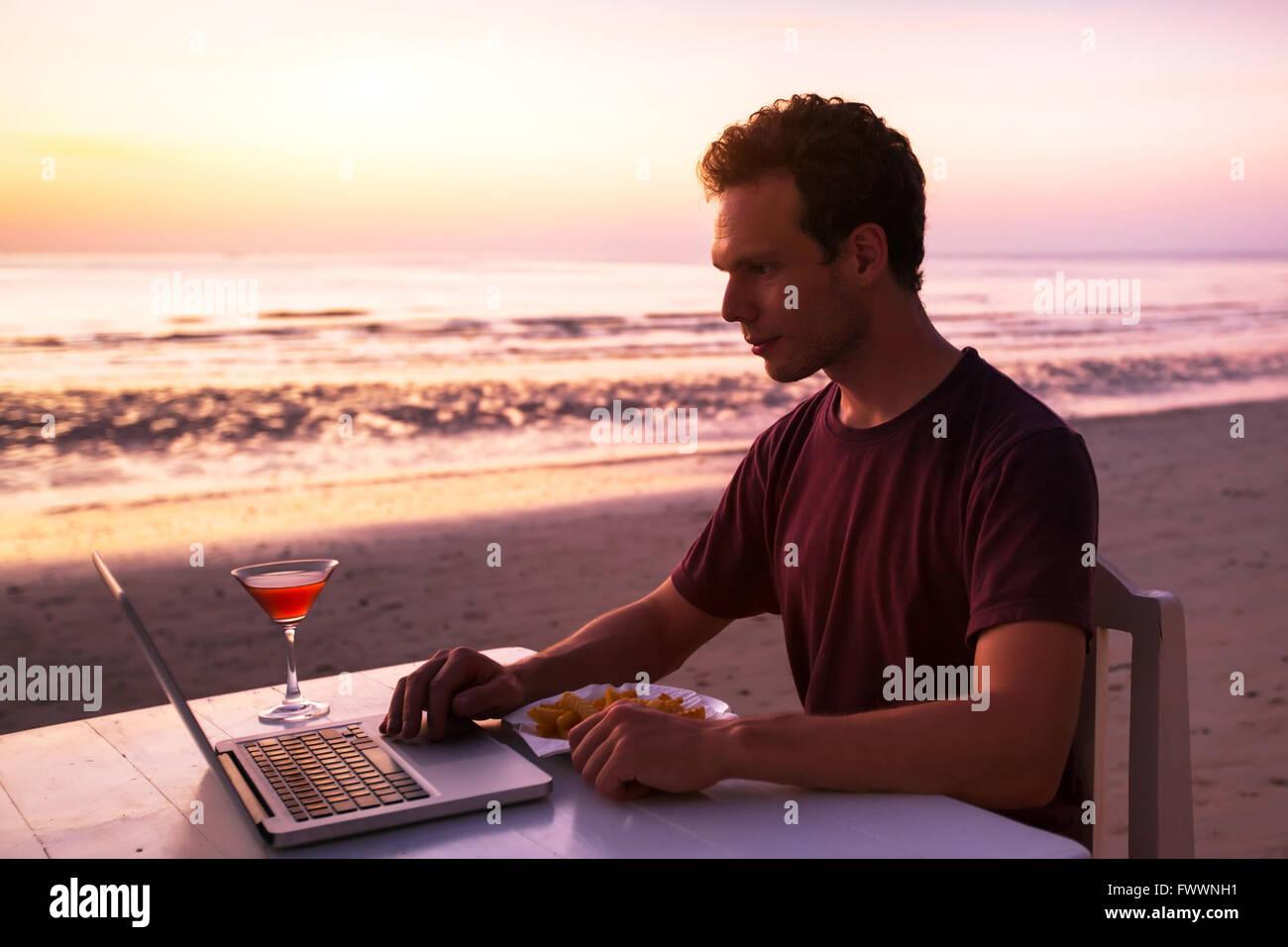 Mann mit Laptop im Restaurant am Strand bei Sonnenuntergang Stockbild