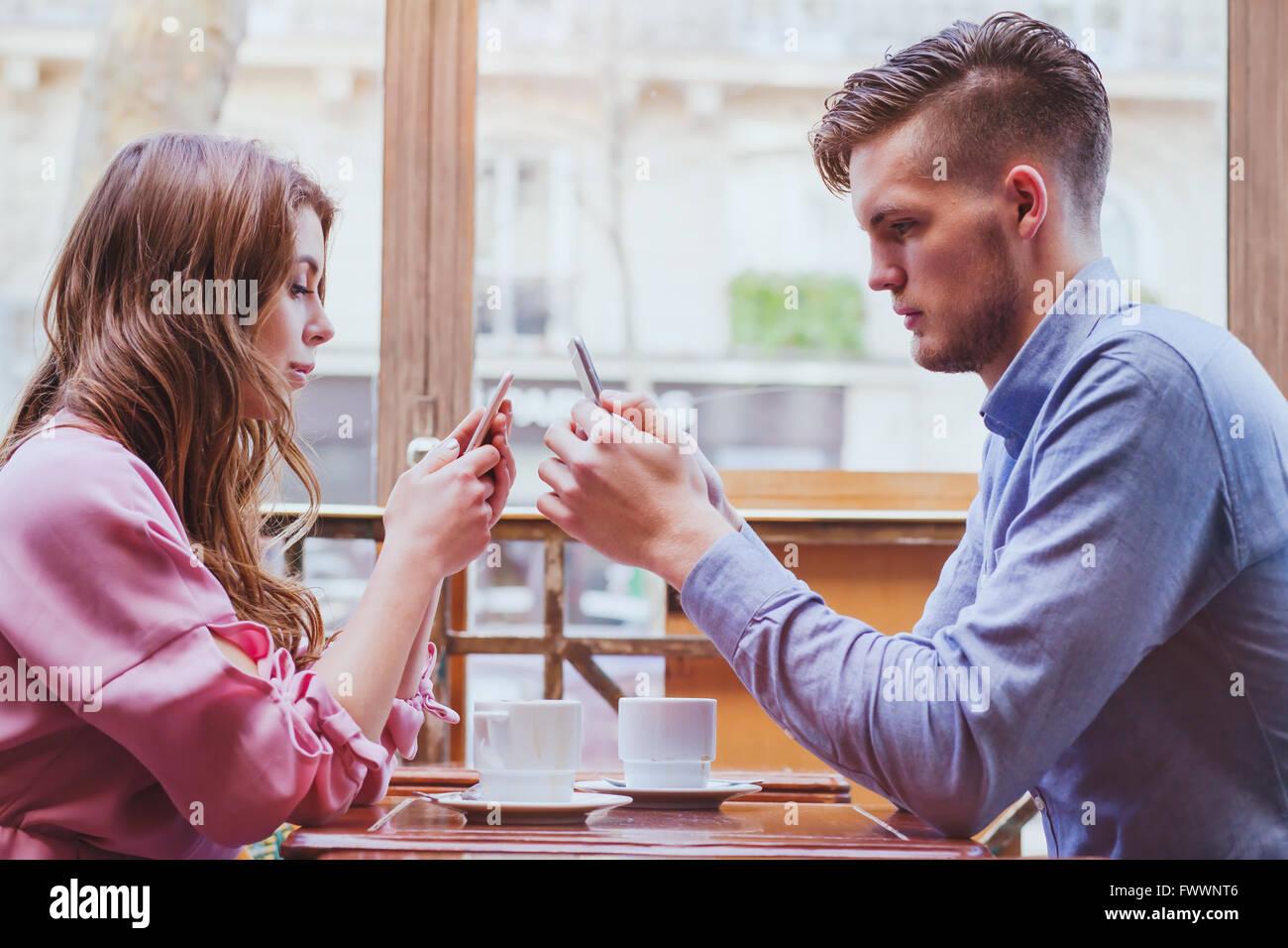 immer verbunden, Internetsucht, junges Paar im Café Blick auf ihren Smartphones, soziale Netzwerk-Konzept Stockbild