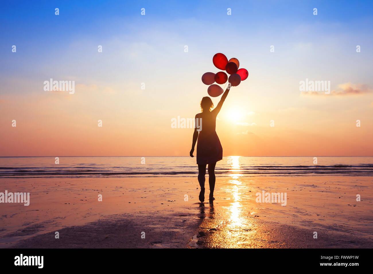 Motivation oder Hoffnung Konzept, folgen Sie Ihrem Traum und Inspiration, Mädchen mit Luftballons bei Sonnenuntergang Stockbild