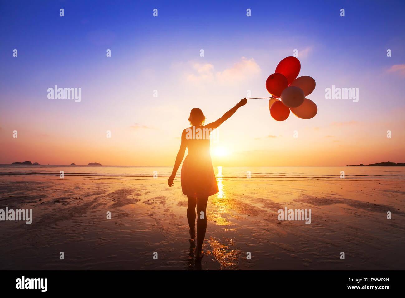 Glück-Konzept, positive Emotionen, fröhliches Mädchen mit bunten Luftballons Sommerstrand bei Sonnenuntergang Stockbild