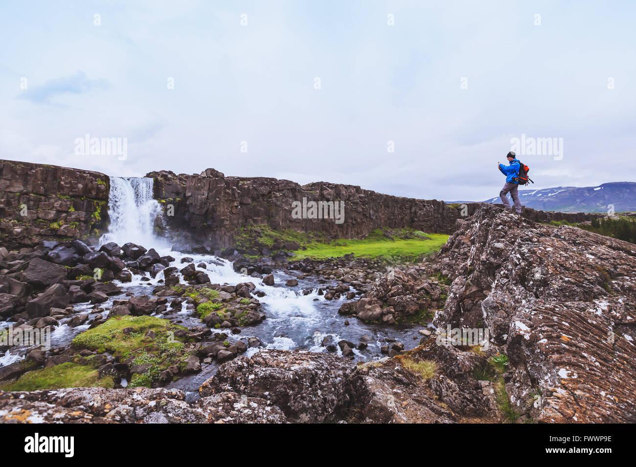 Backpacker Reisenden nehmen Foto des Wasserfalls mit Handy Stockbild