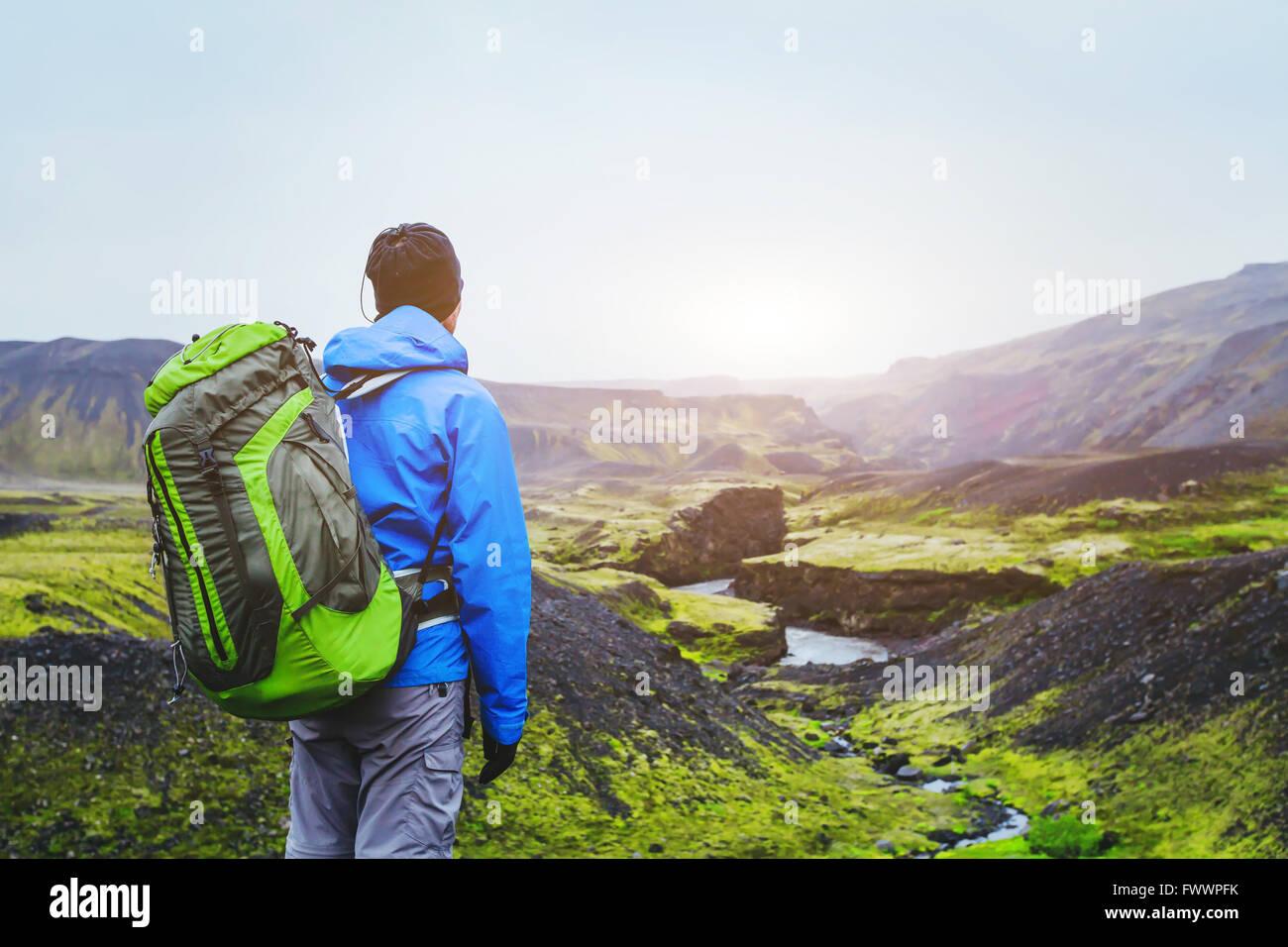 Wanderer mit Rucksack genießen schöne Panoramablick auf Berge in Island, Vulkanlandschaft, Reise-Hintergrund Stockbild