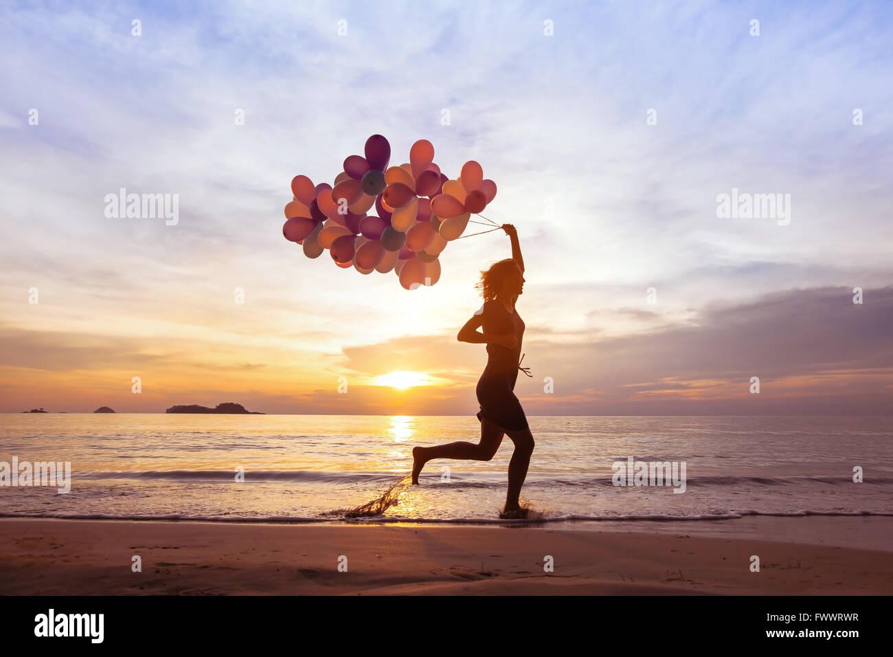 Glück-Konzept, Psychologie von fröhlichen Menschen, junge Frau rennt mit bunten Ballons am Strand Stockbild