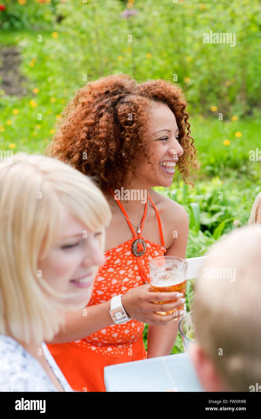 Frau mit lockigem Haar sitzen an Picknick-Tisch mit Glas Bier Stockbild