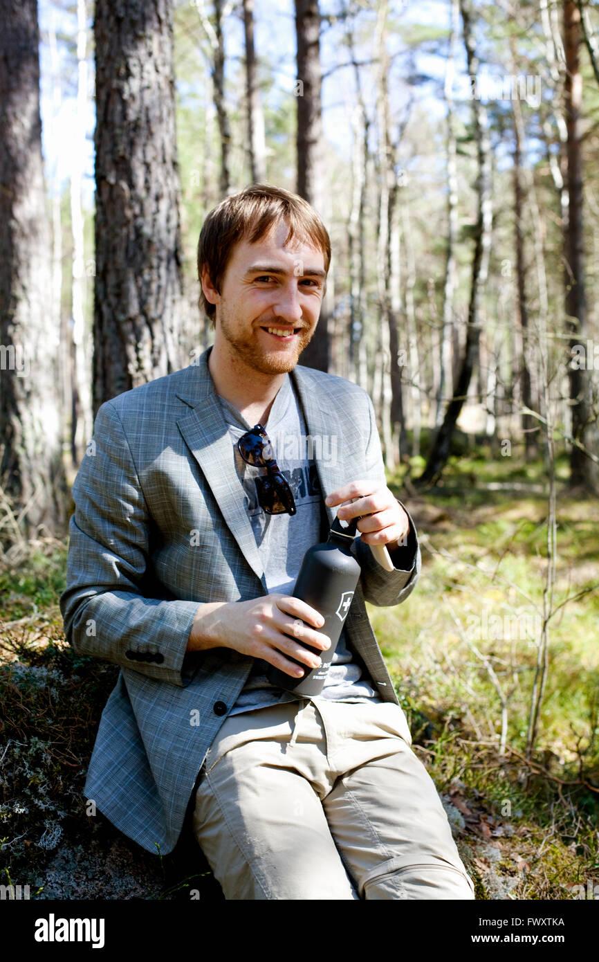 Schweden, Uppland, lächelnd Mann auf dem Rasen sitzen und halten isoliert Getränkeverpackung Stockbild