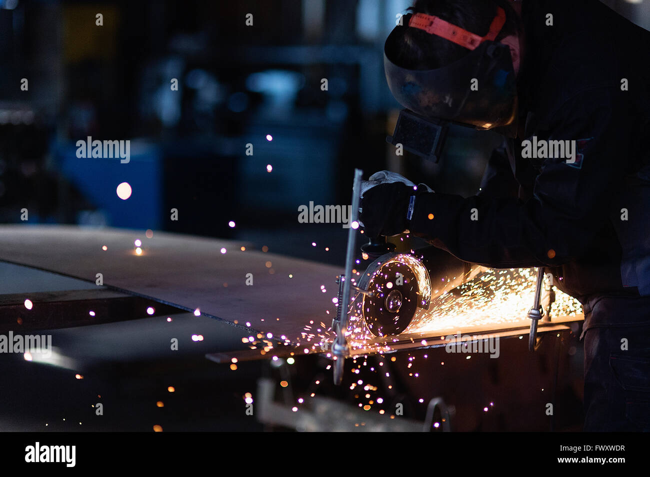 Schweden, junge Mann Schneiden von Metall in Werkstatt Stockbild