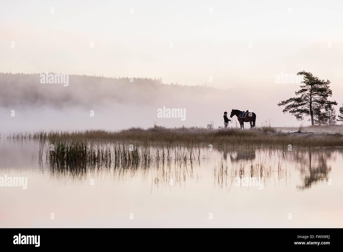 Schweden, Vastmanland, Bergslagen, Hällefors, Grythyttan, Bovik, junge Frau mit Pferd am Seeufer Stockbild