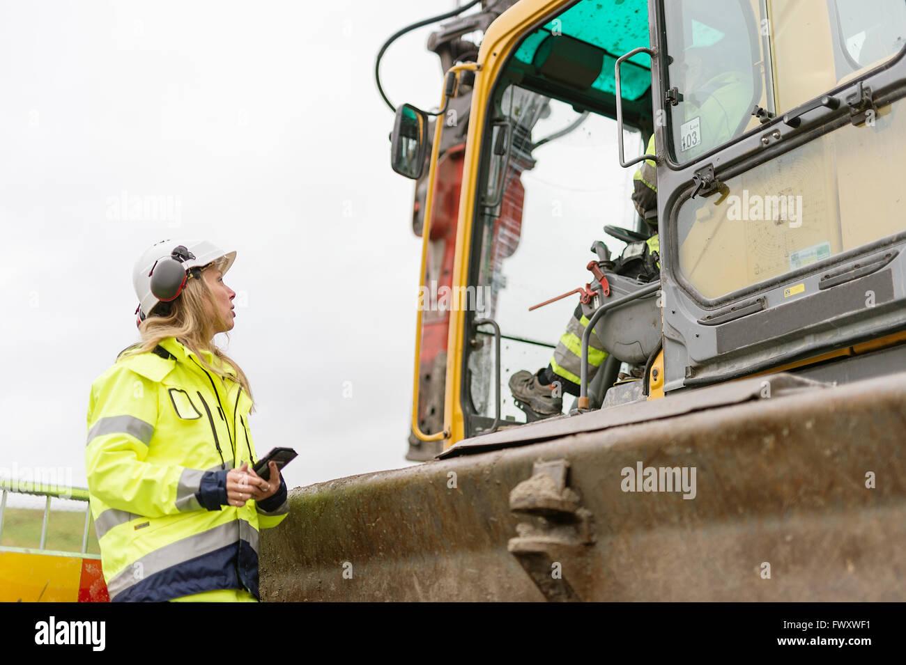 Schweden, Vastmanland, Frau im Gespräch mit Mann im Inneren Bagger auf Baustelle Stockbild