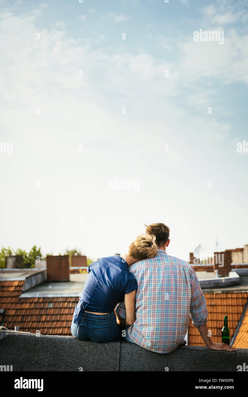 Deutschland, Berlin, junges Paar sitzt auf Dachterrasse mit Bier Stockbild