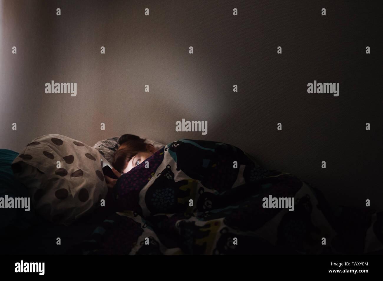 Finnland, junge Frau im Bett liegend und mit Telefon Stockbild