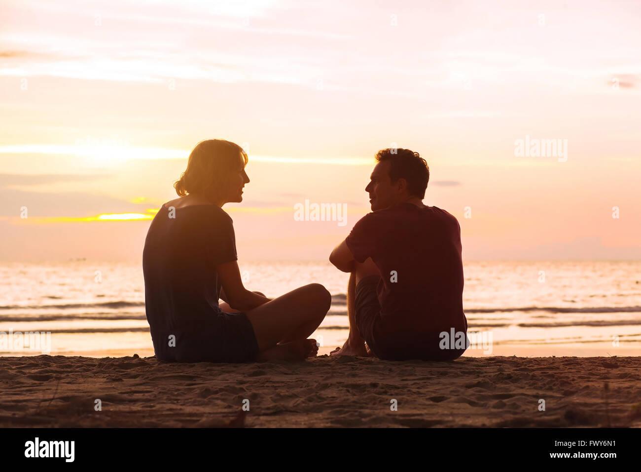 Mann und Frau am Strand bei Sonnenuntergang, junge Paar sprechen in der Nähe von das Meer, dating oder Freundschaft Stockbild
