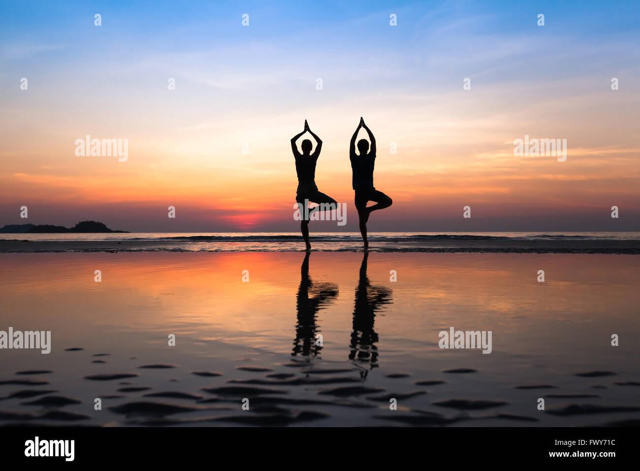 Yoga am Strand, Gruppe von Menschen, die gesunde Lebensweise praktizieren Stockbild