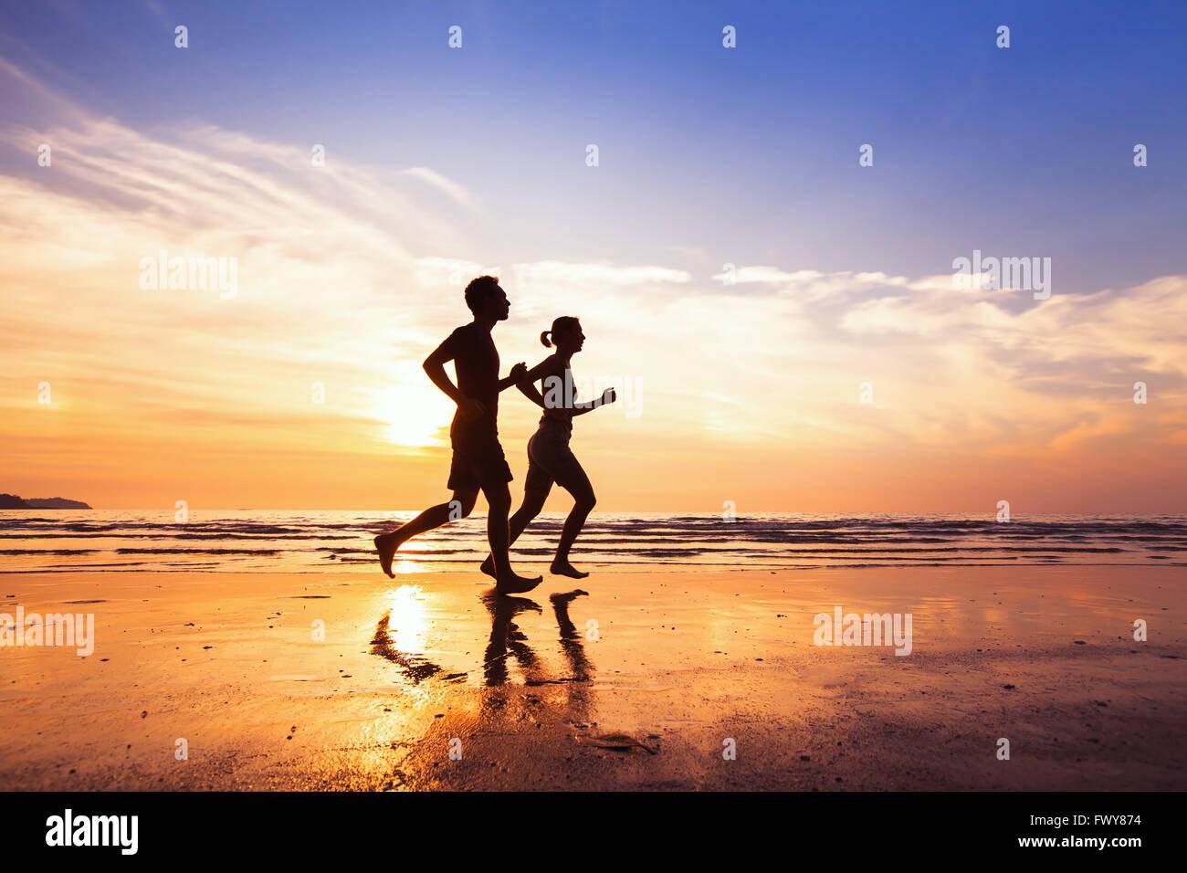 Sport und gesunde Lebensweise, zwei Menschen, Joggen am Strand bei Sonnenuntergang Stockbild