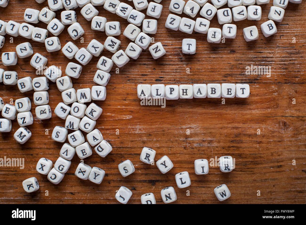 Alphabet-Konzept, Wort, geschrieben mit Holzbuchstaben, weißen englischen Text auf dunklem Hintergrund, abc Stockbild