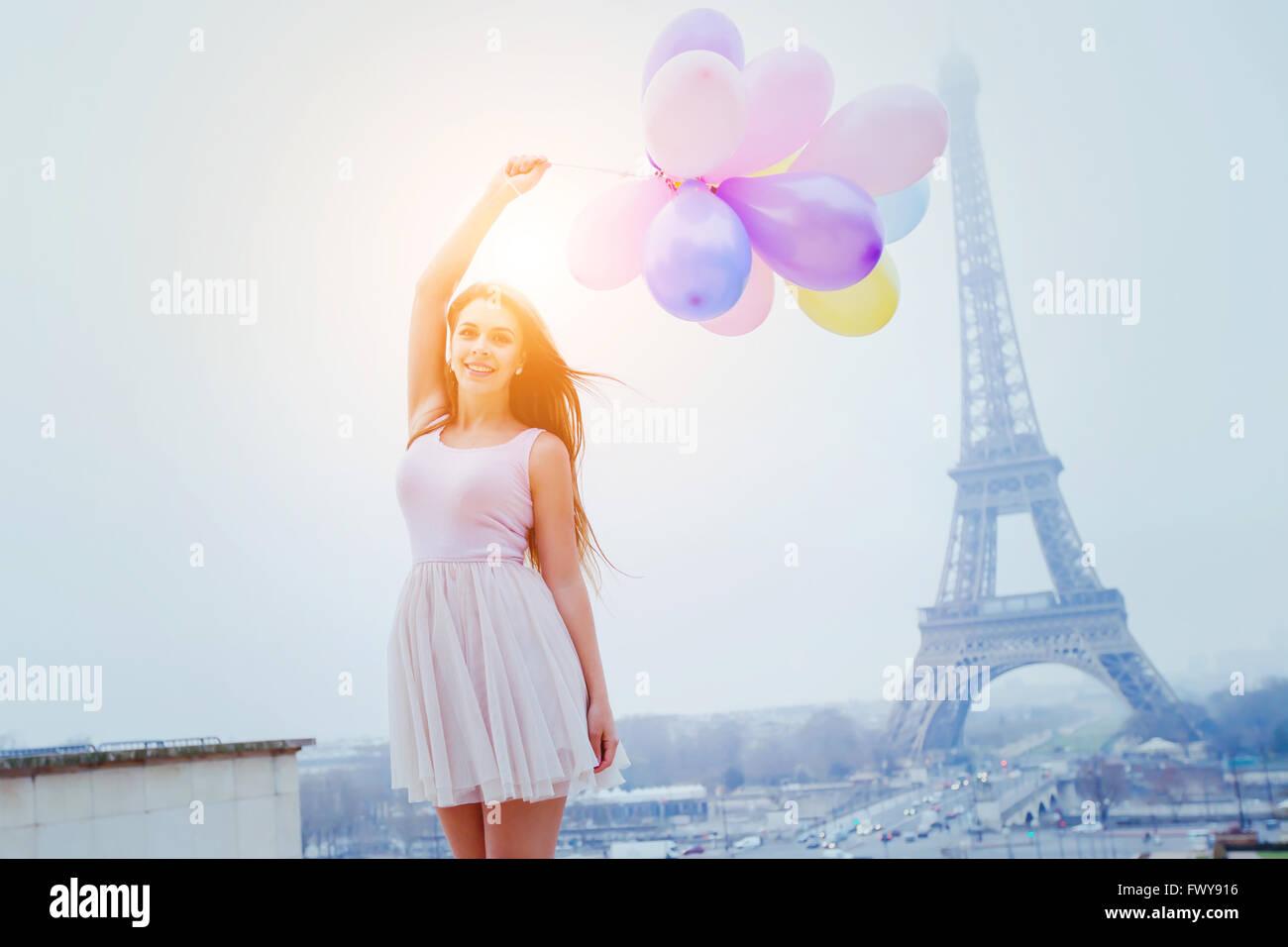Urlaub in Paris, bunte Träume, fröhliches Mädchen mit Luftballons in der Nähe von Eiffelturm Stockbild