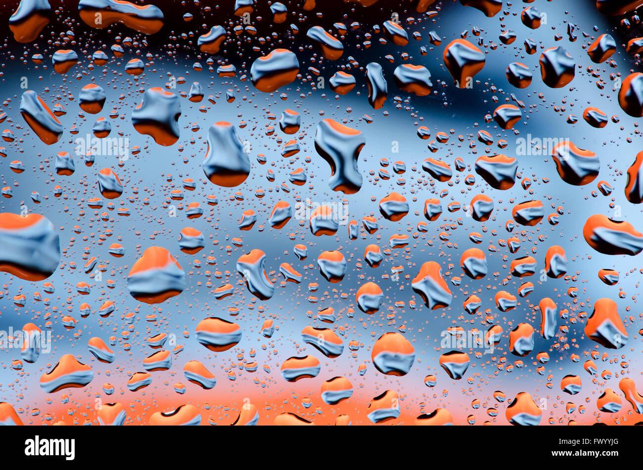 Schwarz blau orangener Hintergrund mit Wasser Tropfen Muster. Stockbild