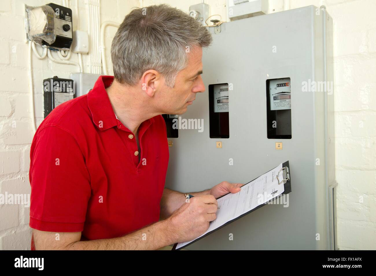Mann liest den Stromverbrauch Stockbild
