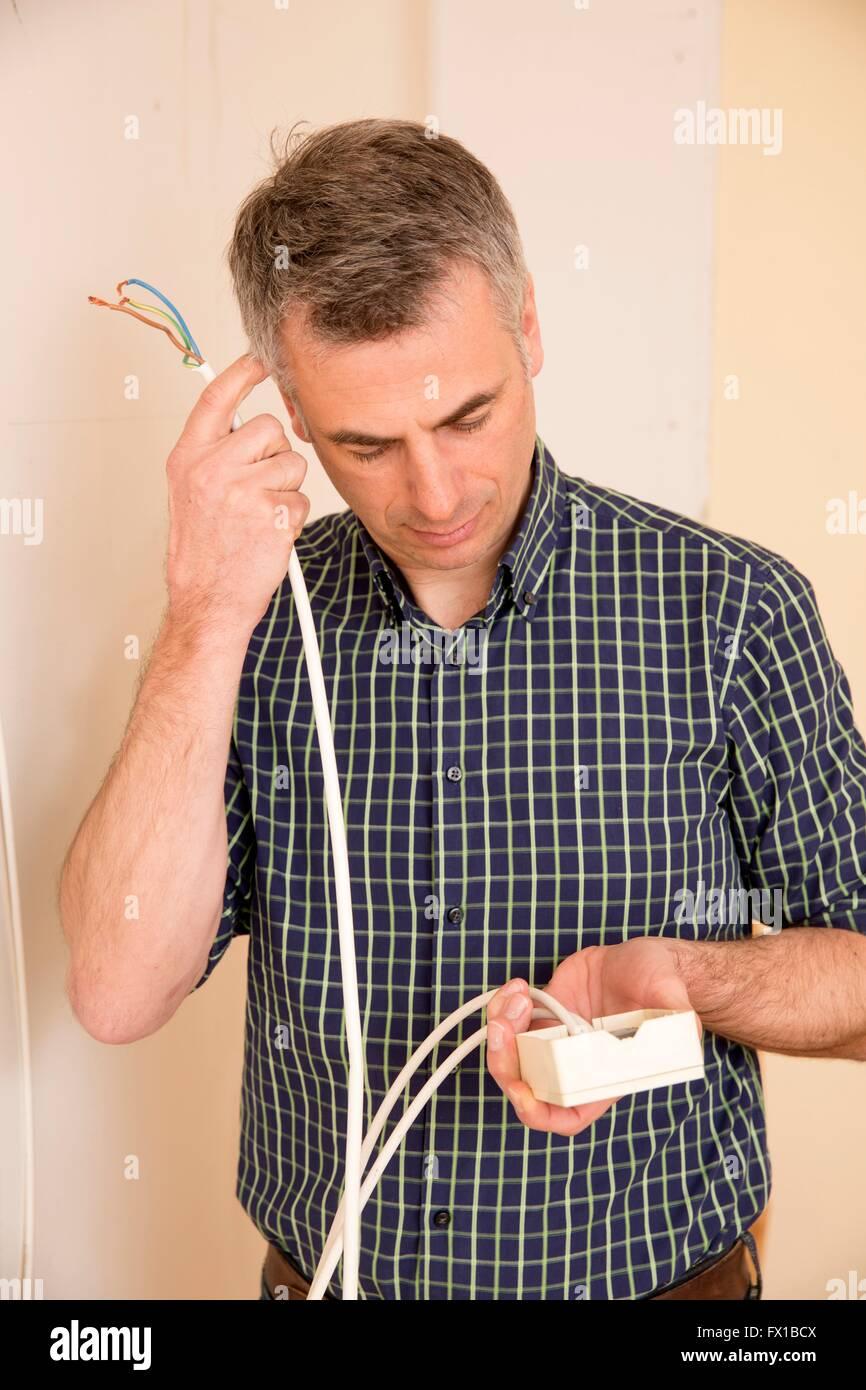 Mann mit Steckdose und Kabel Stockfoto