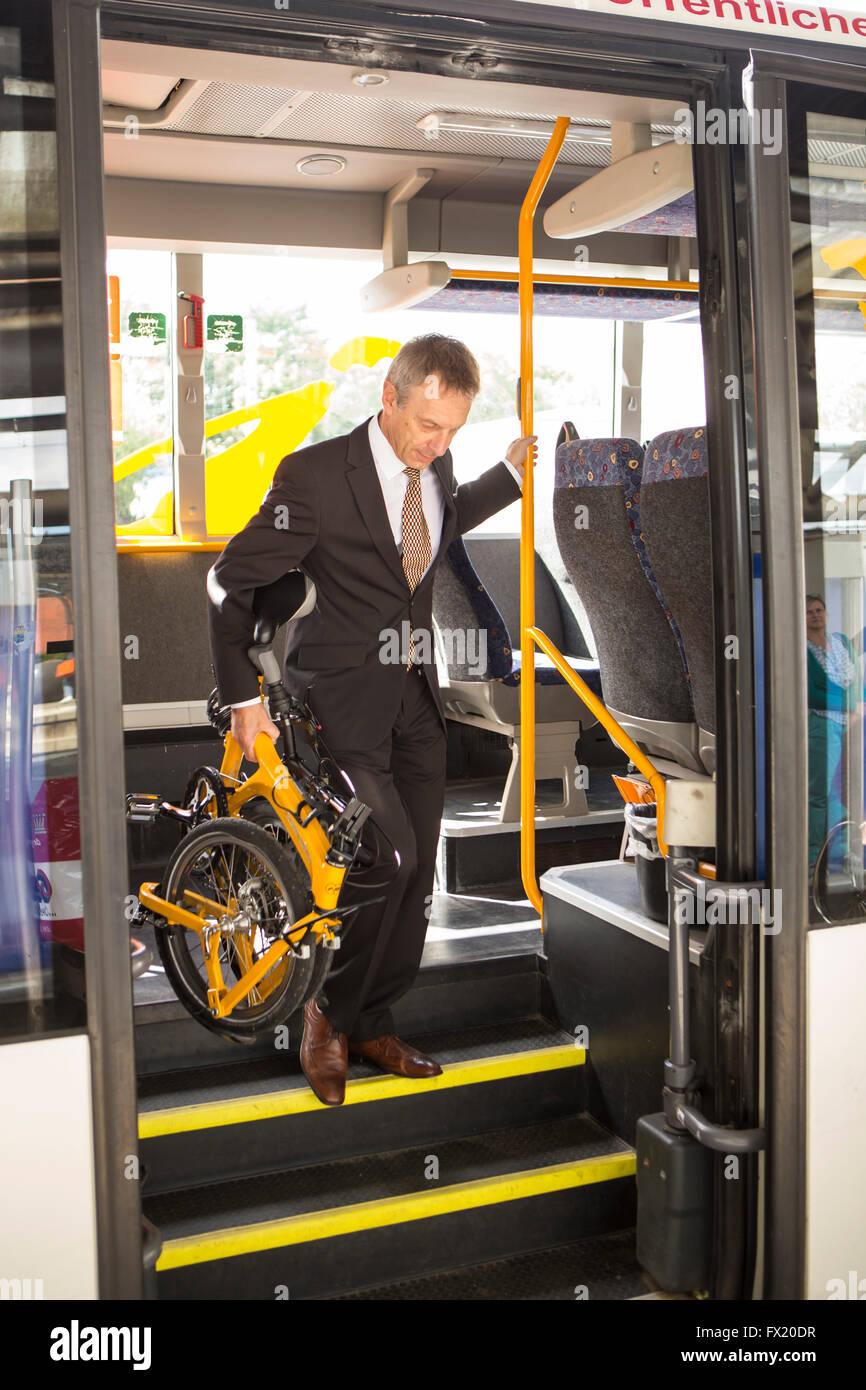 Geschäftsmann mit Faltrad im Bus Stockbild